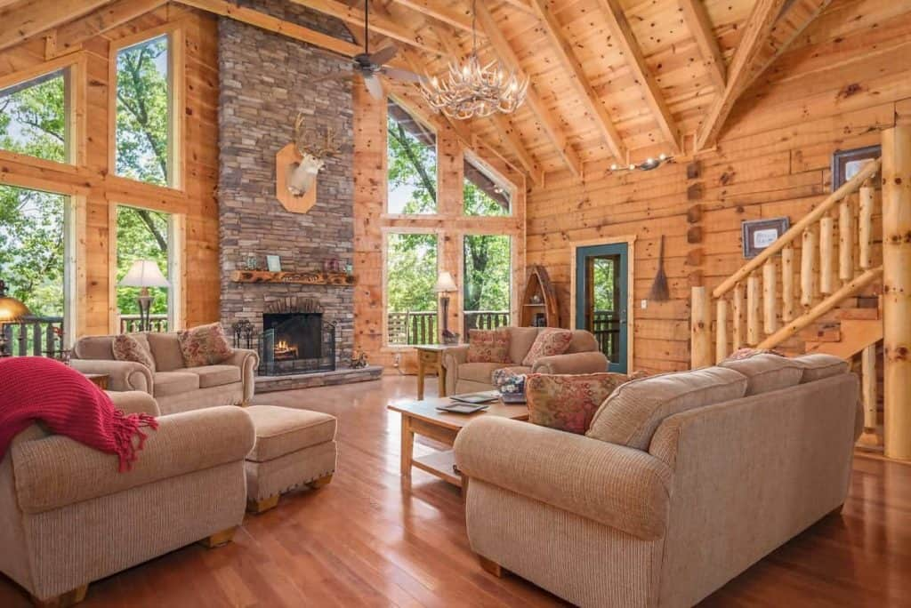 stone fireplace with light brown couches and chairs in wood paneling living room